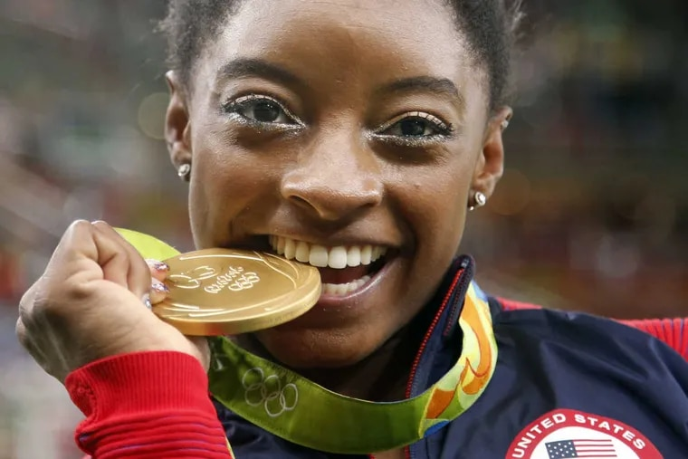 United States' Simone Biles bites her gold medal for the artistic gymnastics women's individual all-around final at the 2016 Summer Olympics in Rio de Janeiro, Brazil, Thursday, Aug. 11, 2016.