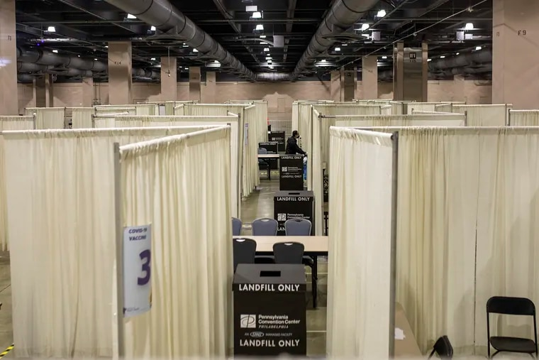 Workers clean up left over trash in the empty COVID Vaccine Clinic at the Philadelphia Convention Center after the city ended its partnership with Philly Fighting COVID.