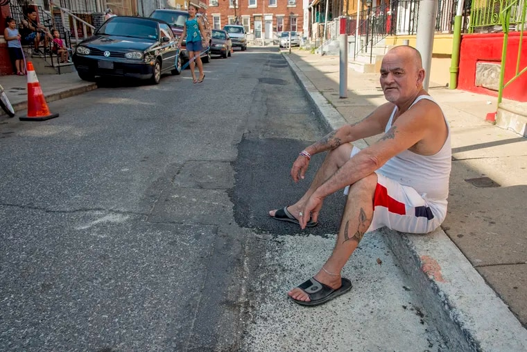 Block captain Faustino Rivera, 65, straddles the pot hole repairs residents made (front) and the recent pothole repair the city did (rear), on the 3300 block of Mutter Street August 9, 2018. Rivera is block captain and residents filled their own potholes after calling the city about it for three years.