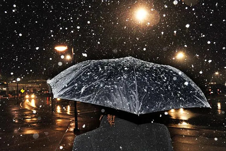 Sherry DeVaughn of Roxborough has her umbrella to shield her from the flurries while taking a break from her job at the King of Prussia mall during a 2013 storm. CLEM MURRAY, File / Staff Photographer