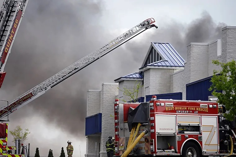 Firefighters work to control a fire in a building in West Berlin, N.J., Thursday, May 8, 2014. The mutli-alarm fire started in Resintech, a 75,000-square-foot manufacturing complex for products to treat water and wastewater. (AP Photo/Mel Evans)