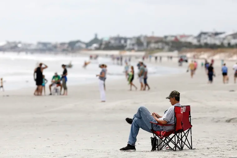 FILE - In this Sept. 13, 2018, file photo, beach goers hang out at the Isle of Palms, S.C., as Hurricane Florence spins out in the Atlantic ocean. Environmental groups plan to sue the Trump administration over offshore drilling tests, launching a legal fight against a proposal that has drawn bipartisan opposition along the Atlantic Coast, two people with direct knowledge of the pending litigation told The Associated Press on Monday, Dec. 10. (AP Photo/Mic Smith, File)