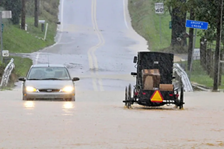 High water on Farmersville Road in Ephrata, Pa., where a car and buggy proceed with caution, tells the story of much of the rain-drenched region Thursday. The worst may be yet to come, when swollen rivers and streams overflow. The National Guard, SEPTA, and Philadelphia police are all on alert for flooding. (Blaine Shahan / (Lancaster, Pa.) Intelligencer Journal)