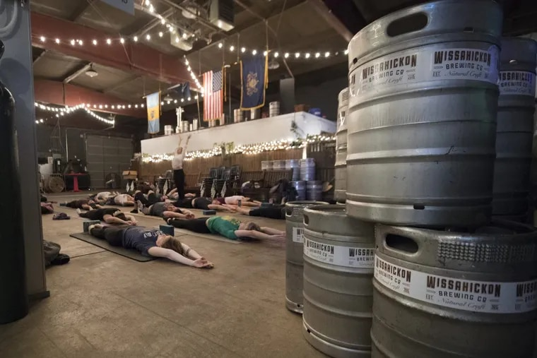 Participants practice yoga during a class in the brewery room at Wissahickon Brewing.