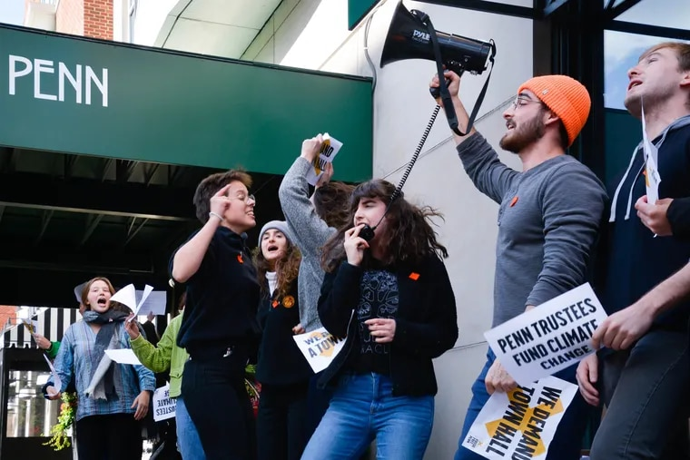 Sophomore Emma Glasser (center with megaphone mic) leads the protest on fossil fuels outside the building when Penn's board of trustees was meeting in November 2019.