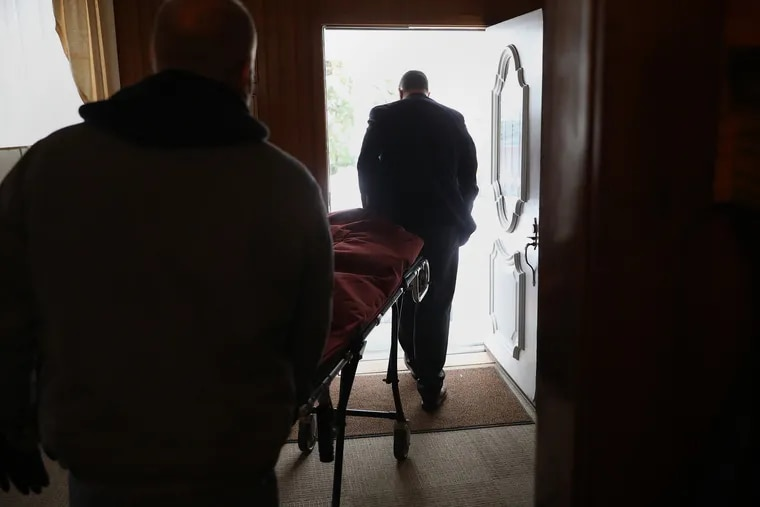 Funeral director Geoff Burke (rear) and employee Sean Wynn wheel an empty stretcher back to their van after disinfecting it at Heller-Hoenstine Funeral Home in Lewistown. Burke is busier than ever as COVID-19 deaths surge across rural Pennsylvania.