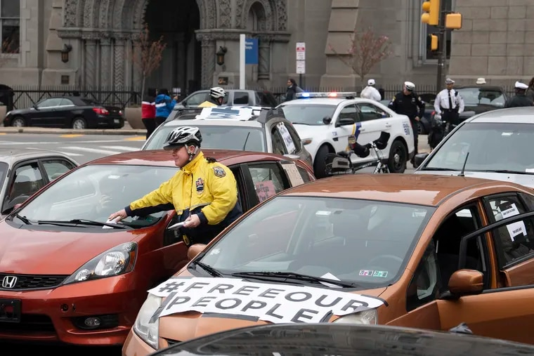 A police officer issues moving violation tickets to a caravan of drivers, who stopped to block traffic in front of Philadelphia City Hall in protest to demand officials free those jails, prisons, and detention centers in response to the COVID-19 outbreak on March 30.