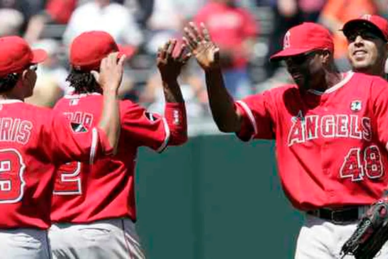 Los Angeles Angels (from left) Maicer Izturis, Eric Aybar, Torii Hunter and Juan Rivera celebrate a victory over the Giants.