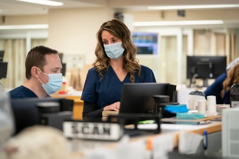 Dr. Chad W. Garson (left) and Karen Fithian, crisis coordinator, discuss possible placements for patients who are experiencing a mental health crisis in the emergency department at Abington Hospital-Jefferson Health.