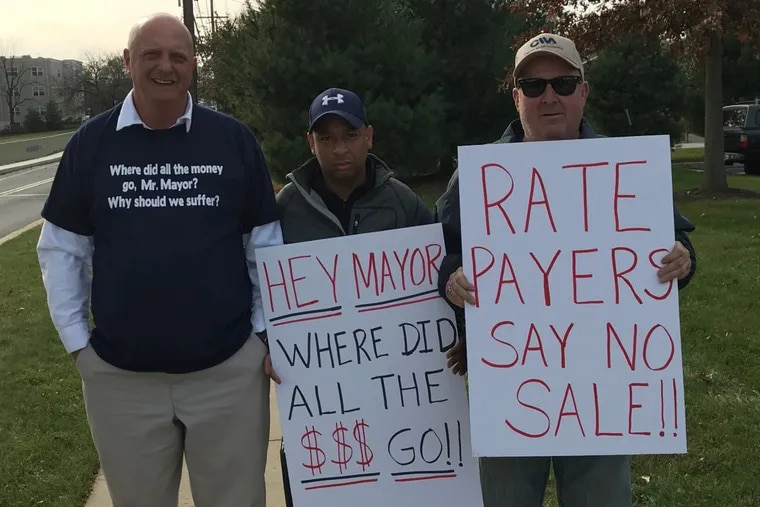Joe Stafford of Upper Chichester (left), Bill Barber of Chester (center), and Ron Navin Upper Chichester protest outside Merenda Hall at Neumann College before a meeting of the Chester Water Authority board, which is split among members from Chester City, Delaware County, and Chester County on Nov. 21.