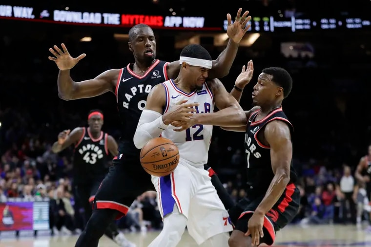 Sixers forward Tobias Harris gets double-teamed late in the fourth quarter by Toronto forward Serge Ibaka (left) and guard Kyle Lowry.