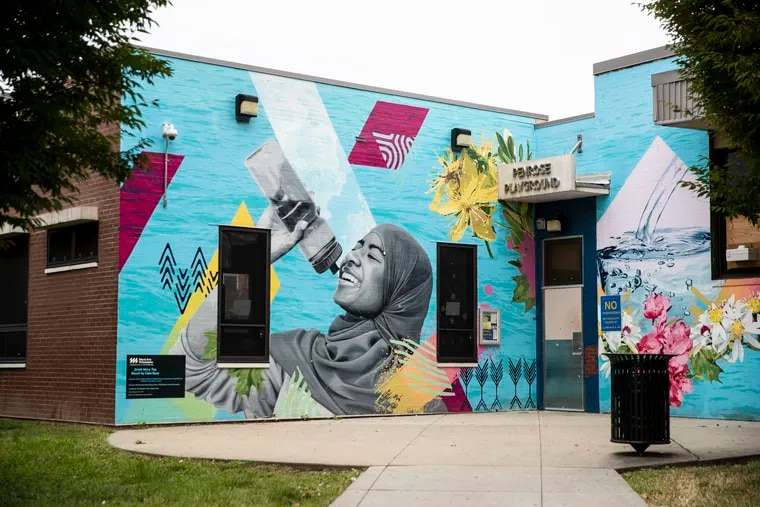 Drink More Tap mural, designed by Salvadoran artist CALO Rosa, at Penrose Recreation Center. The mural features images of local residents and addresses community distrust in tap water.