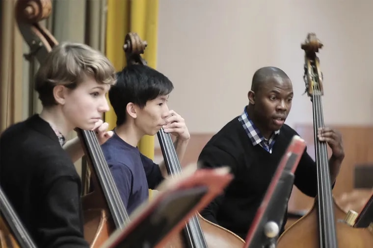 Famed double bassist Joseph Conyers, whose organization Project 440 has taken over the school district's All City Orchestra program, works with members of the bass section during rehearsal. ( ED HILLE / staff photographer )