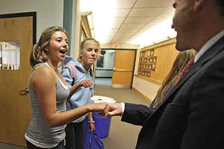 Abington Friends School student Marissa Cotroneo, 13, fist-bumps director Russell Shaw. With her is Sarah Arden. (David M Warren / Staff)