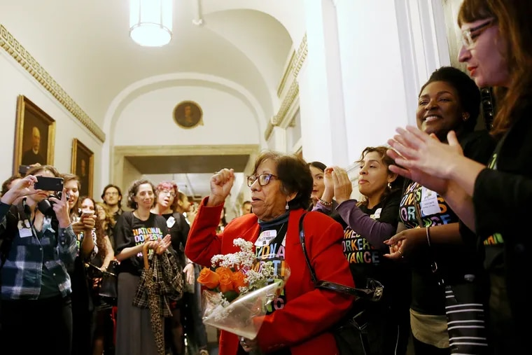 Mercedes Reyes (center) a live-in domestic worker and leader within the Pennsylvania Domestic Workers Alliance, cheers with other advocates after City Council passed a bill expanding labor protections for domestic workers.
