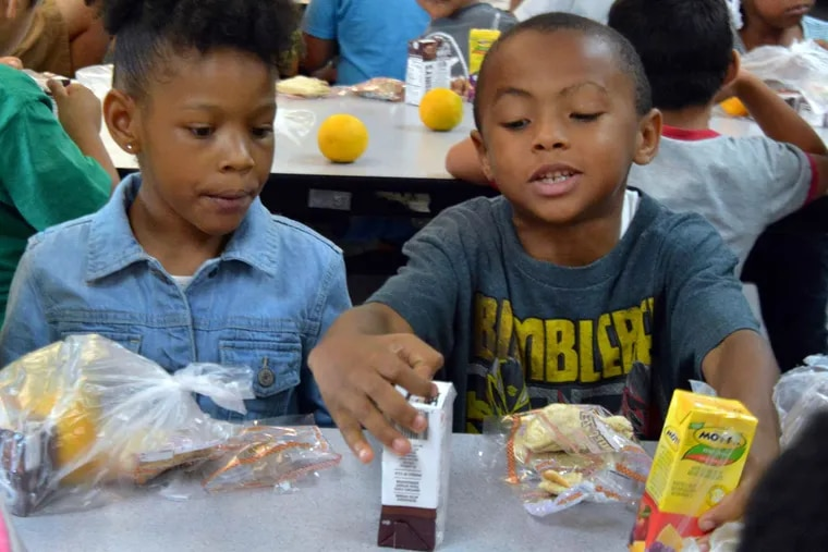 Anivea Allen (left), 6, and Zachary Cruz, 7, enjoy lunches provided by the Food Bank of South Jersey at the Camden Community Charter School. The program serves Burlington, Camden, Gloucester, and Salem Counties.