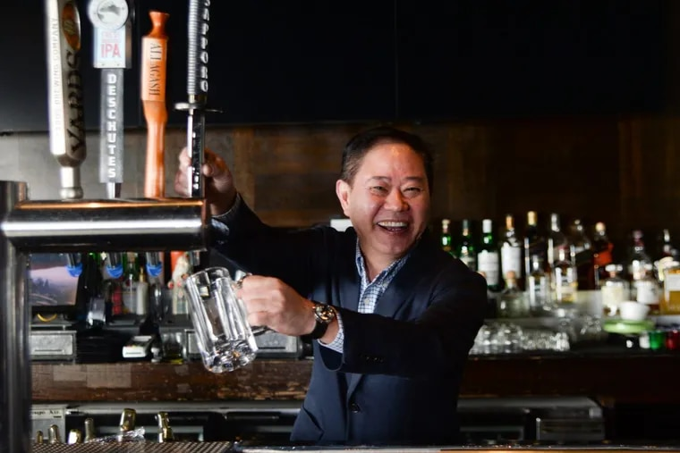 Jimmy Shen, owner of Yakitori Boy in Chinatown, prepares to pour a drink.