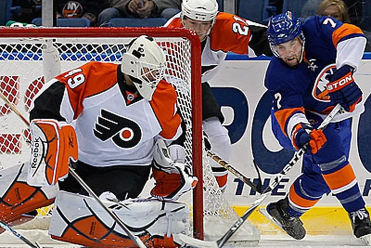 Islanders winger Trent Hunter takes a shot as Michael Leighton defends. The Flyers have won three straight with Leighton in goal. (AP Photo/Kathy Willens)