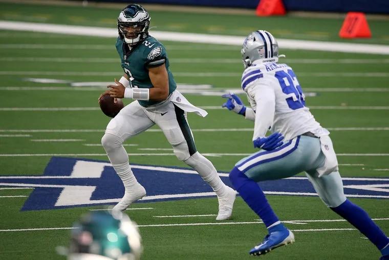 Eagles quarterback Jalen Hurts scrambles away from Cowboys defensive end Dorance Armstrong during the second quarter.