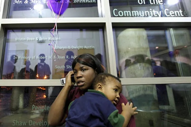 Shantell Thomas talks on the phone as she holds her son, Jabari Bartlett, while the two attend an Anti-Violence Night at the Homan Square Community Center in North Lawndale, Illinois. (Heather Charles / Chicago Tribune/MCT)