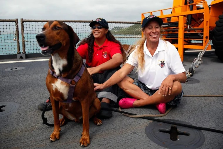 Jennifer Appe (right) and Tasha Fuiava sit with their dogs on the deck of the USS Ashland on Monday  at White Beach Naval Facility in Okinawa, Japan.