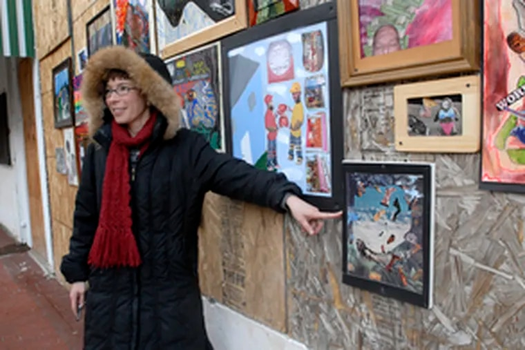 """Elizabeth Demaray, an associate professor at Rutgers-Camden, leads a critique of the paintings on display on Market Street in Camden. """"I attempt to encourage outreach from the university to the community,"""" Demaray said."""