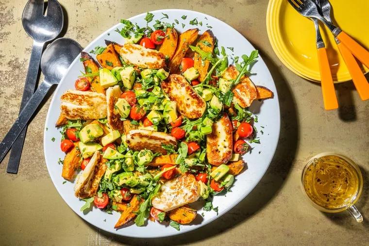 Fried halloumi, arugula and tomato salad with avocado and sweet potatoes.