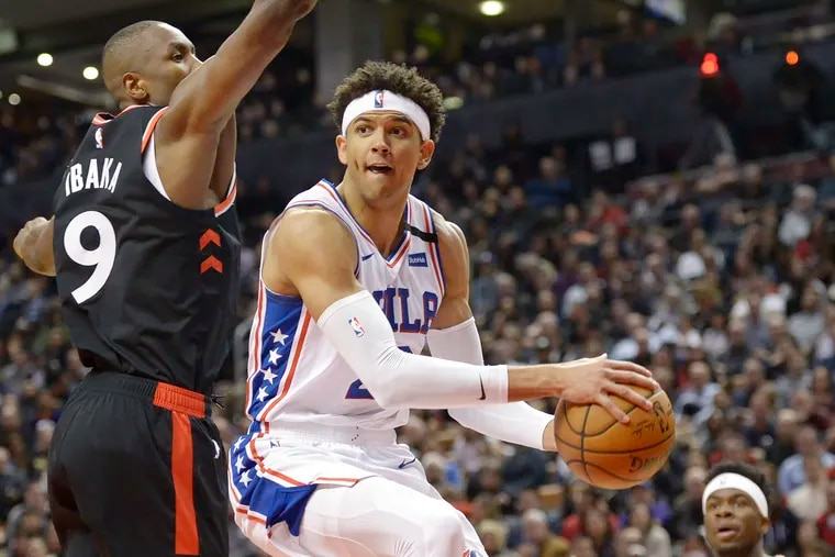 76ers guard Matisse Thybulle passes the ball around Toronto Raptors forward Serge Ibaka during the second half.