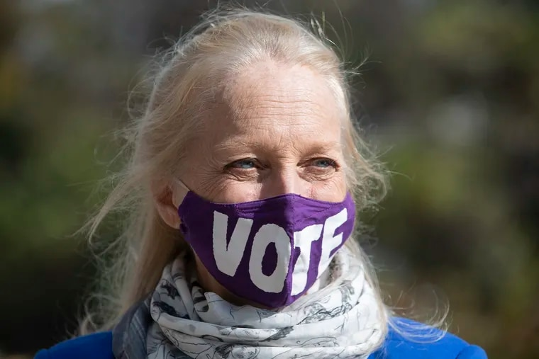 """U.S. Rep. Mary Gay Scanlon (D., Pa.) wears a """"Vote"""" mask as she stops at a polling location in Brookhaven, in Delaware County on Election Day."""