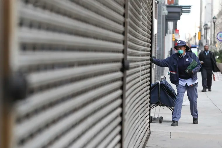 A postal worker heads down Chestnut street in Center City on Tuesday, March 24, 2020. Non-essential businesses are closed and a stay-at-home order has been issued by the city, with the exception of those working for life-sustaining businesses, due to the spread of the coronavirus.