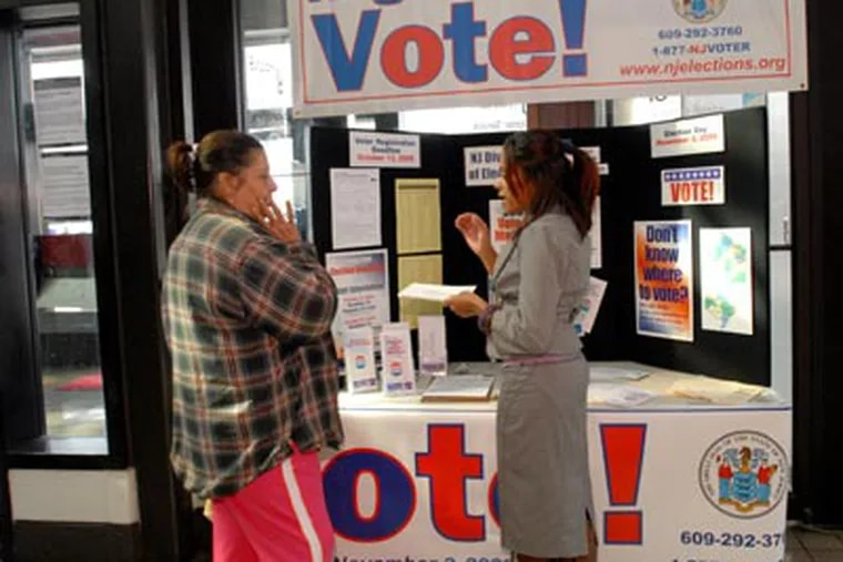 At the Walter Rand Transportation Center in Camden, officials register voters and hand out mail-in voting materials. Here, Madeline Rodriguez, right, gives info to Agripina Vega of Cherry Hill. ( April Saul / Staff Photographer )