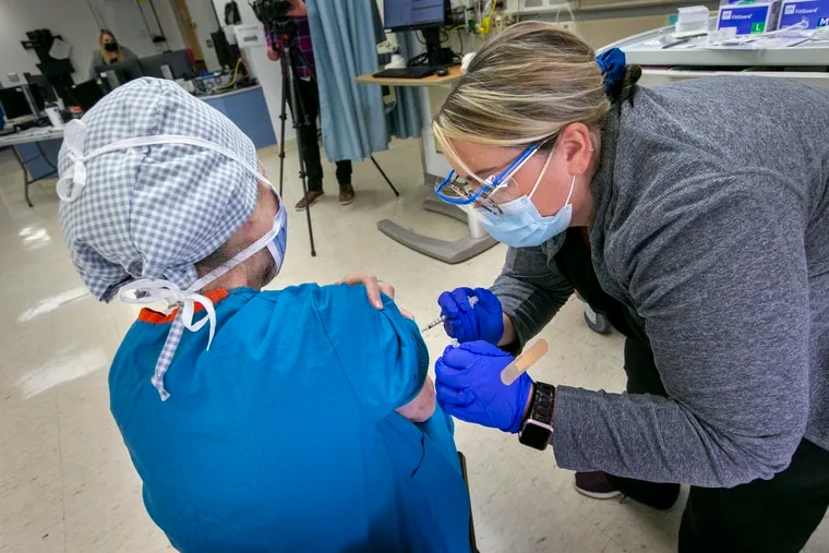 Registered nurse Erin Gallagher administers the COVID-19 vaccine to Bonnie Karpo, operating room nursing educator at St. Christopher's Hospital for Children, in December.