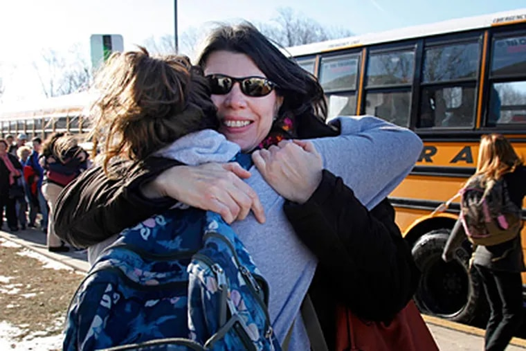 Kristen Gware, right, embraces her daughter, Hallie Gware, who plays the alto sax with the Downingtown West High School marching band. The students gathered at Downingtown East High School to board buses for the airport Tuesday morning. (Laurence Kesterson / Staff Photographer)