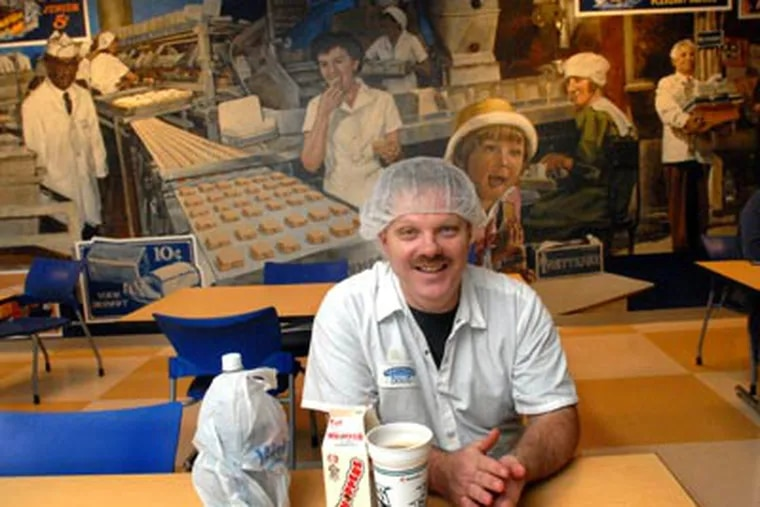 Oven operator Doug Miller sits in front of a mural in the Tastycake Baking Co. cafeteria at its new location in the Naval Business Center. (April Saul / Staff Photographer)