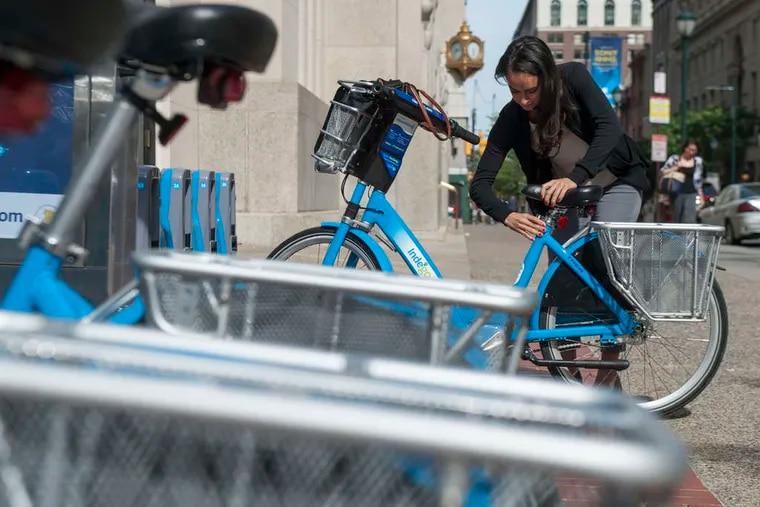 MICHAEL PRONZATO / STAFF PHOTOGRAPHER Tara Jennings prepares to take an Indego bike home from work.