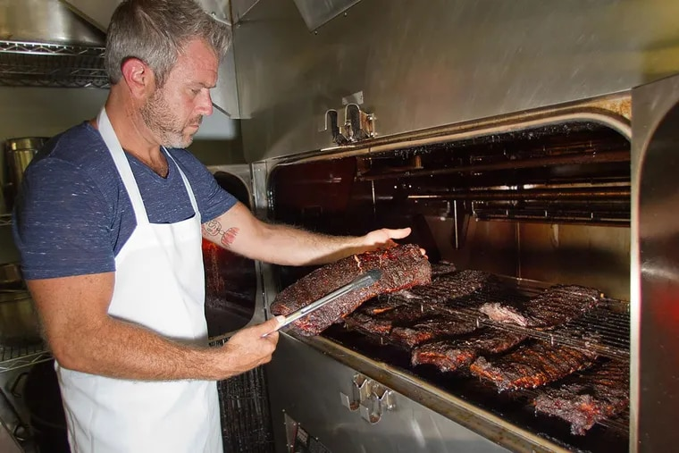 Chef-owner Chad Rosenthal checks on racks of ribs cooking in the smoker at The Lucky Well, 111 E Butler Ave, Ambler.