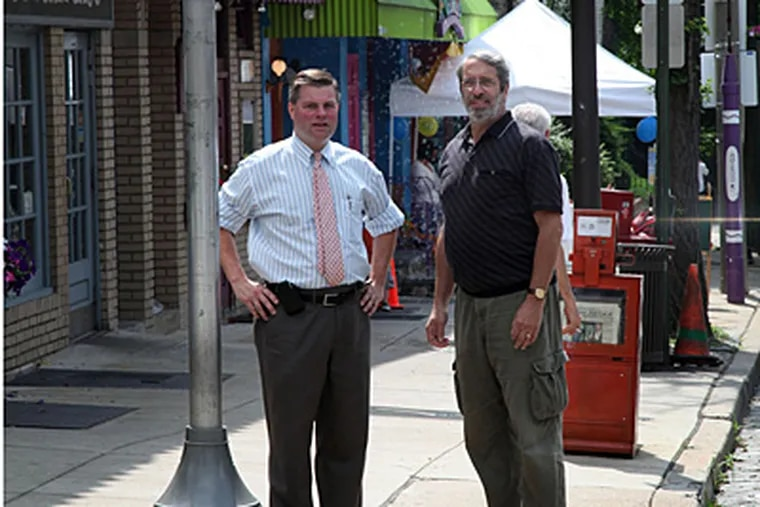 Fran O'Donell, manager of the Chestnut Hill Business Association, left, and Greg Welsh, association president, at the corner of Gravers Lane and Germantown Avenue in Chestnut Hill.  (Laurence Kesterson / Staff Photographer )