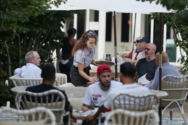 Server Alexa Zackowski (center) brings drinks to customers at Suraya in Philadelphia's Fishtown section on Tuesday, Aug. 11, 2020. The restaurant's garden is open for outdoor dining during the coronavirus pandemic.