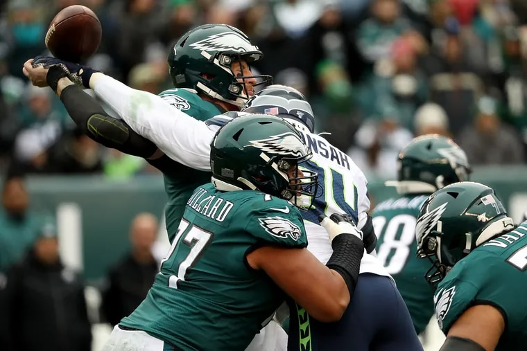 Eagles quarterback Carson Wentz is hit by Seattle defensive end Ezekiel Ansah as he tries to throw during the loss on Nov. 24.