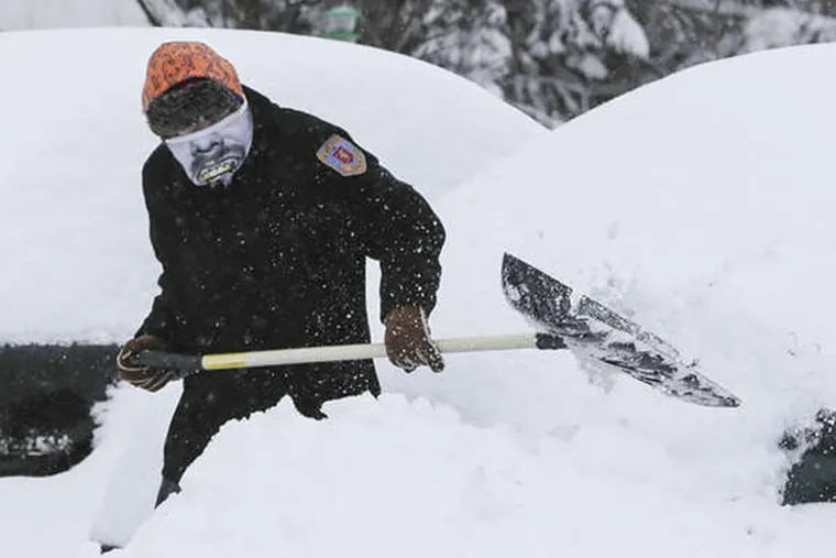 Alex Neff of East Pikeland, Chester County, digs out his two cars on Feb. 13, 2014. STEVEN M. FALK / Staff Photographer