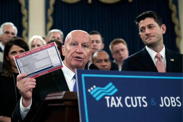 """House Ways and Means Committee Chairman Kevin Brady (R., Texas), joined by House Speaker  Paul Ryan (right), holds a proposed """"postcard tax filing form"""" as they unveil the GOP's far-reaching tax overhaul."""