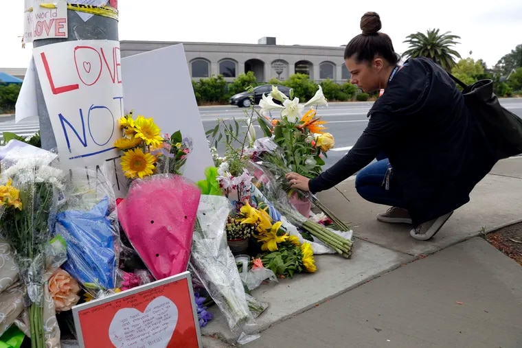 A woman leaves flowers on a growing memorial across the street from the Chabad of Poway synagogue in Poway, Calif., on Monday,, April 29, 2019. A 19-year-old gunman opened fire on Saturday as about 100 people were worshipping exactly six months after a mass shooting in a Pittsburgh synagogue, killing one and injuring more.