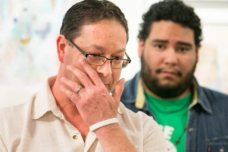 Paul Frame shows emotion while speaking about his husband, who has been detained by ICE, as Miguel Andrade, Communications Manager of Juntos, back right, looks on at a press conference at the William Way Center in Center City.