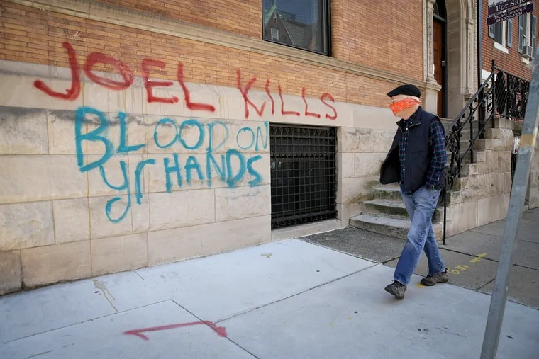 An unidentified pedestrian passes the vandalized home belonging to Joel Freedman at 21st and Locust Streets in Philadelphia, PA on April 6, 2020. Freedman is the owner of Hahnemann University Hospital.
