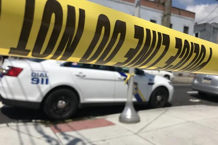 Crime scene tape and a Philadelphia Police car.