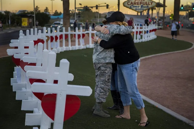 Sharon Black of Las Vegas, right, hugs Airmen First Class Williams of the U.S. Air Force after they were both overcome with emotion while viewing wooden crosses bearing the names of those killed during last month's mass shooting.