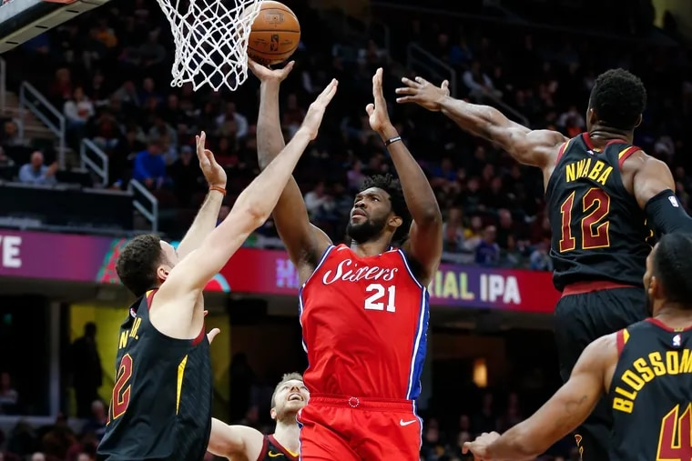 Joel Embiid (21) goes up for two among Cleveland's Larry Nance Jr. (left), David Nwaba (12), and Jaron Blossomgame (foreground, right) on Sunday.