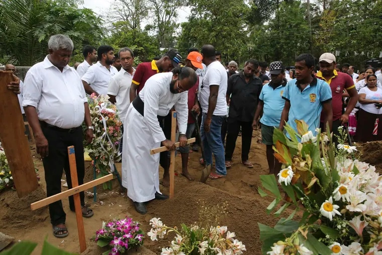 Father Niroshan Perera places a cross during the funeral service of Dhami Brandy, 13, who was killed during Easter Sunday's bomb blast at St. Sebastian Church, in Negombo, Sri Lanka Thursday, April 25, 2019.