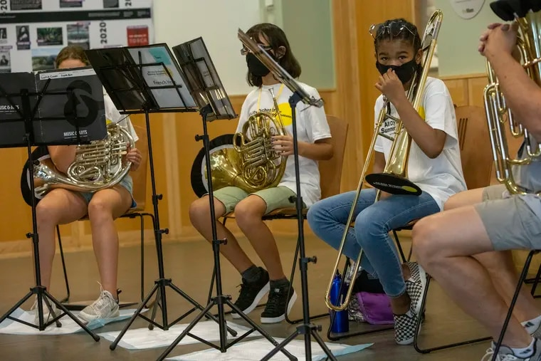 Chrysyn Harp, a 7th grader at the Girard Academic Music Program, playing trombone with Brass Chamber Ensemble  at the All-City Orchestra Summer Academy at Mann Music Center on July 27. Mask wearing at school can be challenging, but it's essential, doctors say.