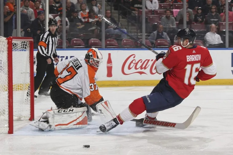 Flyers goalie Brian Elliott defends the net as Panthers center Aleksander Barkov (right) is tripped wile shooting in the Flyers' 3-2 loss to the Panthers.